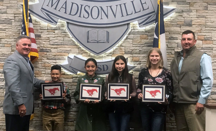Madisonville CISD Students of the Month (from left) Tyrenzo Garrett (Elementary), Azul Avila (Intermediate), Jaydee Torres (Junior High) and Harmony Schmidt (High School) pose with Superintendent Keith Smith (left) and MCISD Board Member Bo Williams at the monthly meeting for November on Monday.