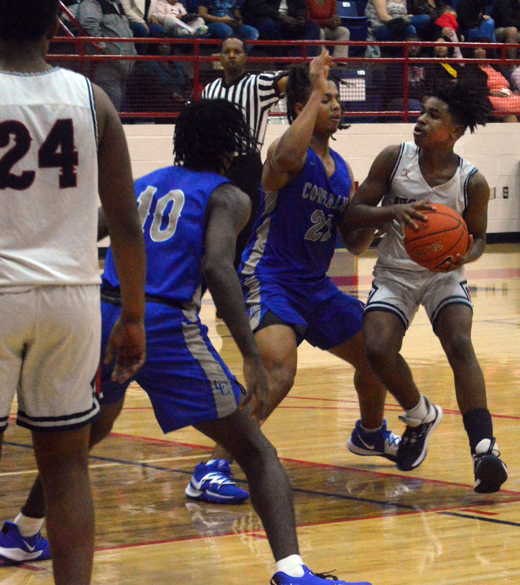 Madisonville's Xzavier Whaley looks for an open man during a Mustangs home game at MHS.