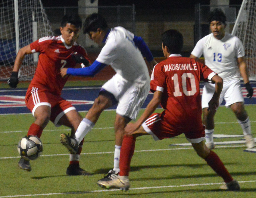 Madisonville's Gabriel Aceves fights an opponent for the ball during a Mustangs home game at MHS.