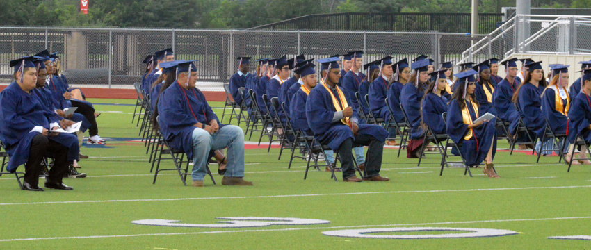 MHS graduates spaced evenly apart on the football field of Mustang Stadium Thursday.