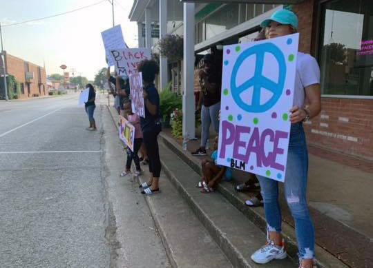 Citizens gather on the sidewalk next to Highway 21 on the Madisonville square with signs to make their voices heard in response to demonstrations throughout the county after the killing of an African American man named George Floyd in Minnesota May 25.