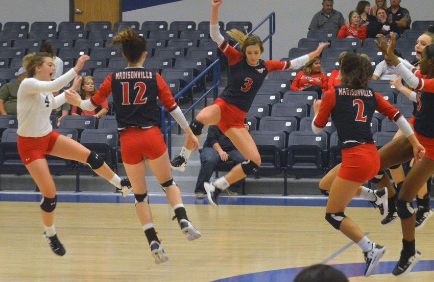 Members of the 2019 Madisonville Lady Mustangs volleyball team celebrate a successful point during a Bi-District victory over Huntington in Crockett Nov. 5.