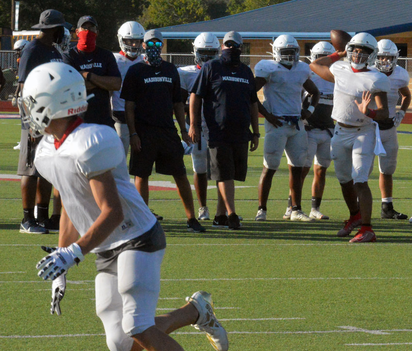 Madisonville coaches look on as quarterback Armando Juarez finds an open man before Thursday's scrimmage against Cameron at MHS. The Mustangs will open their regular season against Diboll Friday at 7:30 p.m. The game has been moved to MHS.