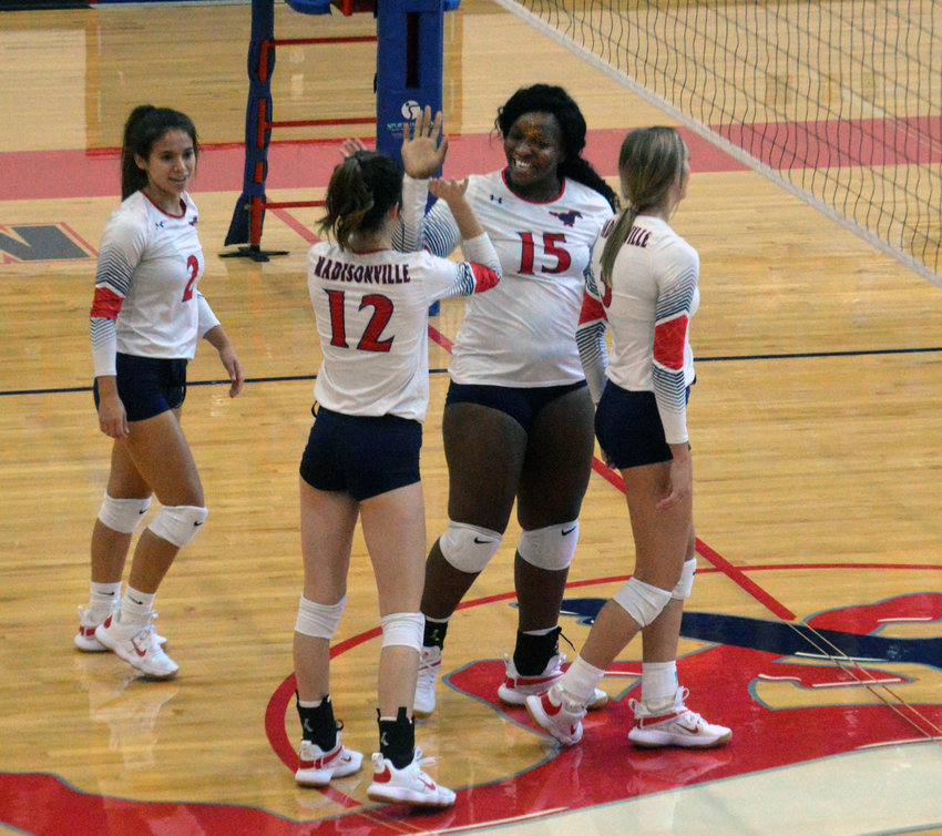 Brianna Johnson (15) is congratulated by teammates Grayson Bennett (12), Chloe Olvera (2) and Grace Williamson (3) following a block in a victory over North Zulch at MHS Aug. 18.