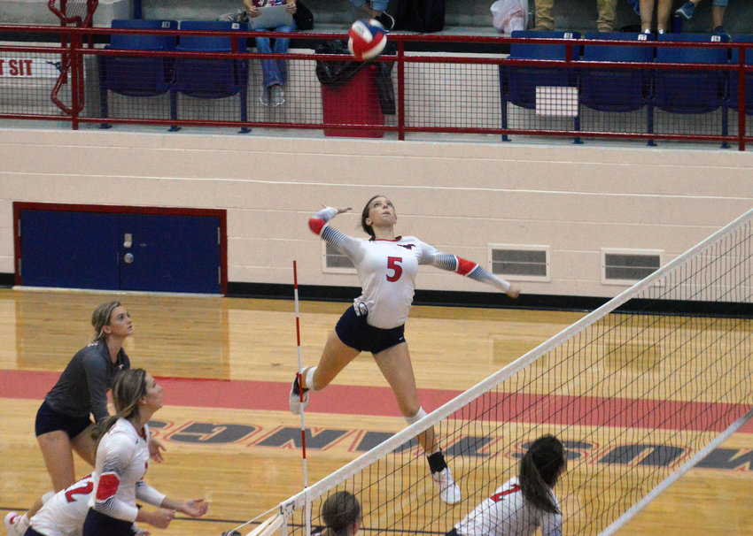 Kourtney Fleck goes high for a kill during Madisonville's victory over Corrigan at MHS Friday.