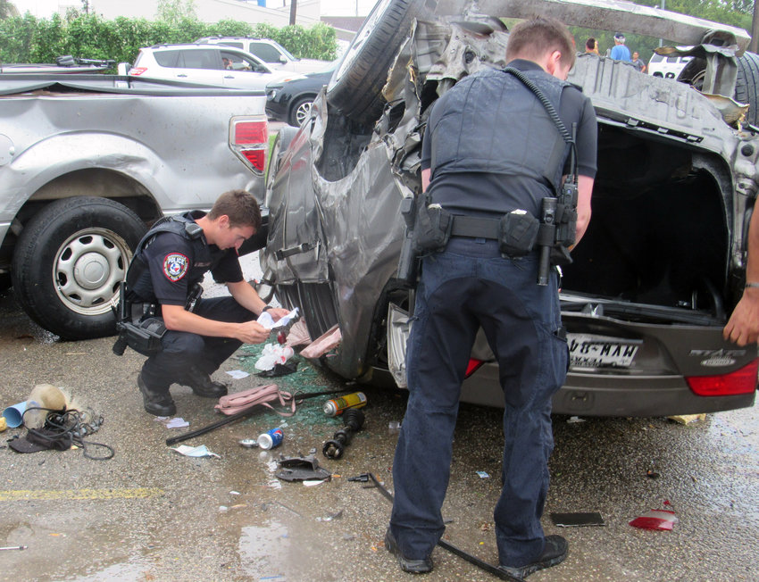 Madisonville Police Officer Michael Bellard and other law enforcement officials inspect the result of a violent crash off Highway 21 in Madisonville Tuesday, in which the vehicle ended up in the parking lot of the Madison County Sheriff's Office.