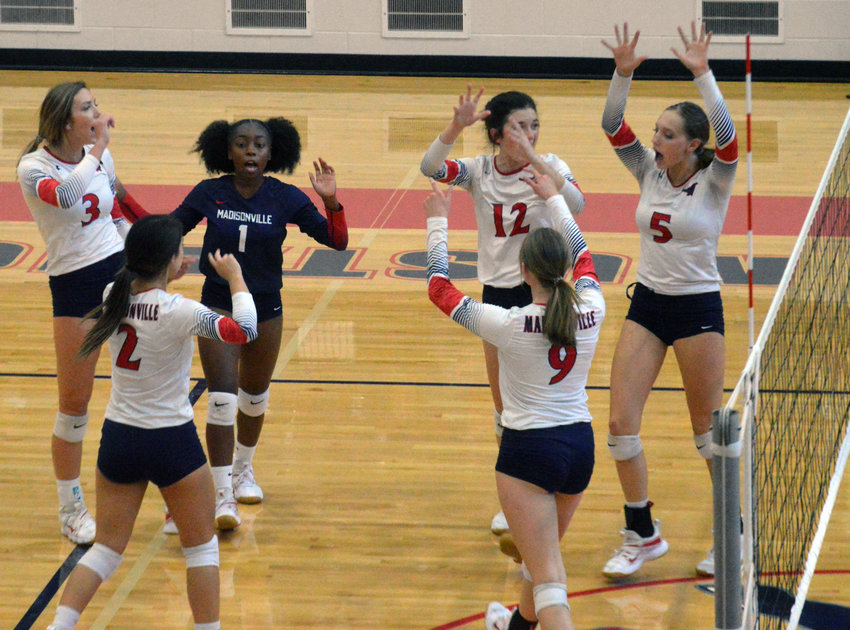 Members of the Madisonville volleyball team celebrate a successful point during Friday's district win over LaVega at MHS.