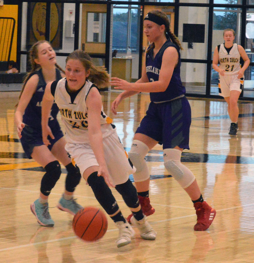 Lakin Madden of North Zulch looks dribbles between defenders in Saturday's homecoming loss at NZHS.
