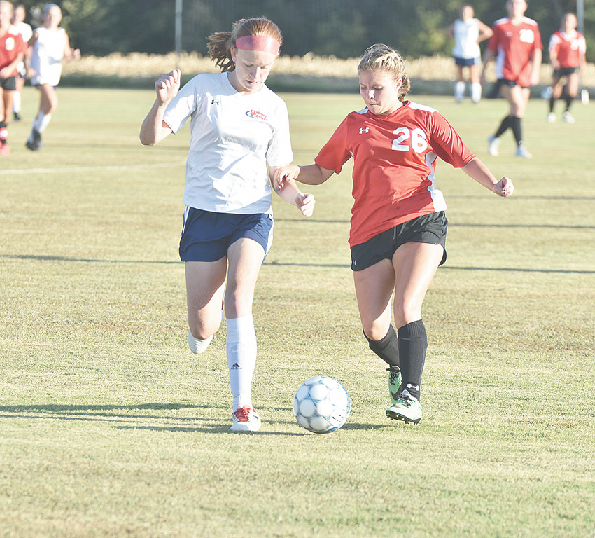Lady Rebel Julianna Cole (right) battles for control of the ball.