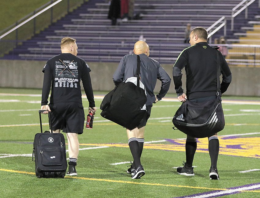 Soccer officials leaving the field after suspending the game with three minutes left in the contest.