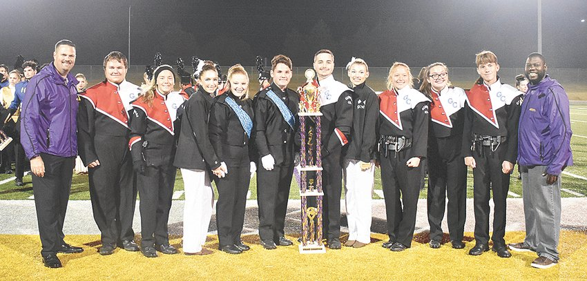 Bethel University Renaissance Regiment Directors Keith Cottrill (left) and Tremayne Johnson present the Grand Champion trophy to Gibson County High School.