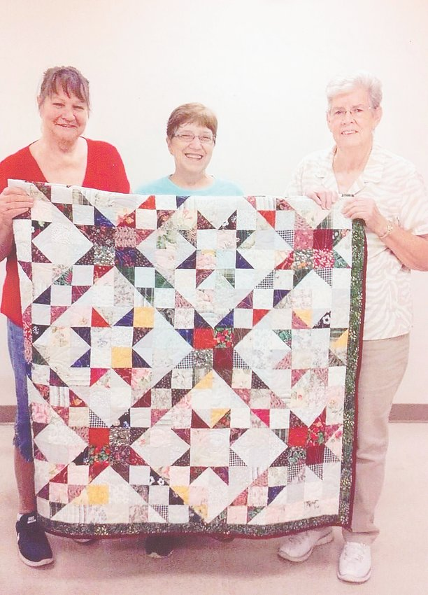 Silver Threads Quilt Guild members Ruby Heatly (left) and Mary Towater (right) help display the patchwork quilt being donated to Habitat for Humanity. Representative Becky Scates (center) was present to accept the quilt, which will be used at the Habitat for Humanity gala to raise funds. Silver Threads is proud to support Habitat for Humanity.