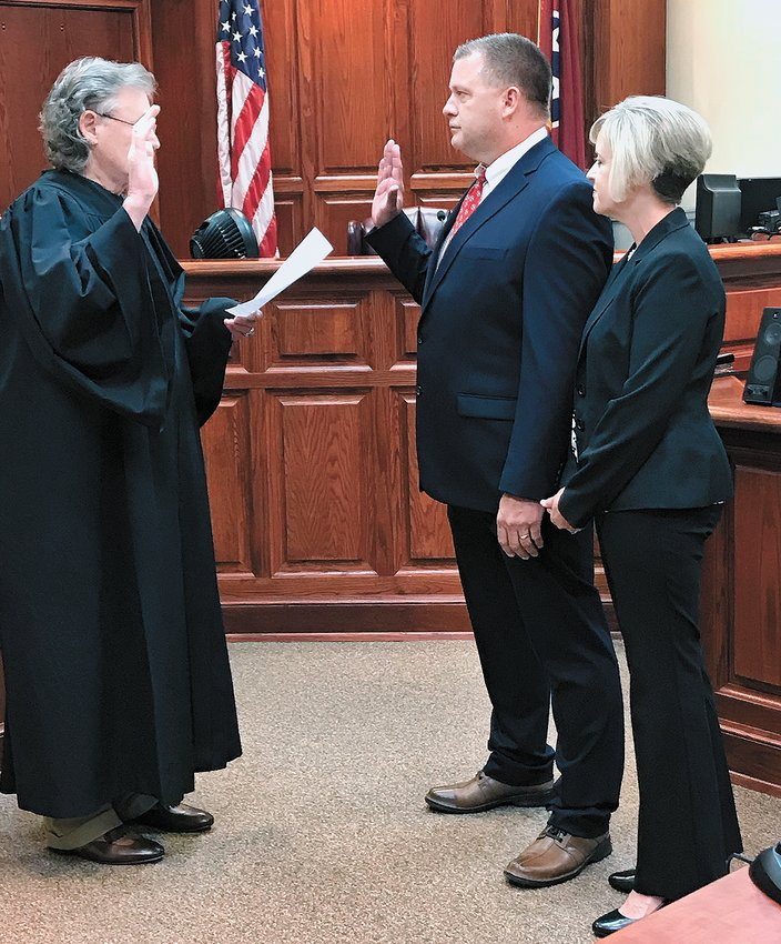 Carroll County General Sessions Judge Larry Logan administers the oath of admission to Tim Nanney as Carol Nanney looks on.