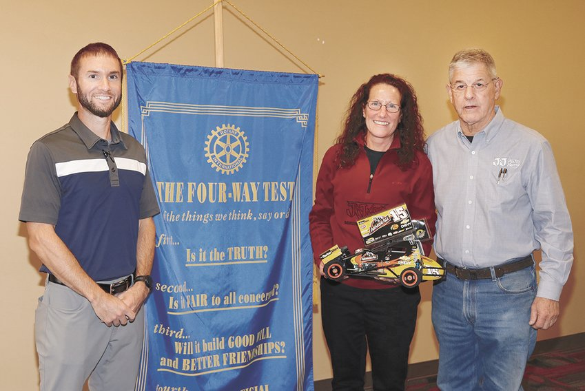 Rotarian Mark Smith with Bonnie and Jack Elam, owners of J&J Racing in McKenzie. Bonnie holds a miniature replica of a sprint car.