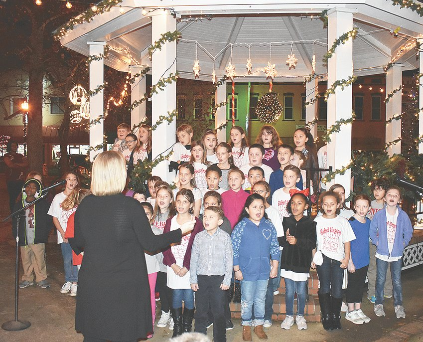 The third grade Rebel Singers, under the direction of MES music teacher Joanna Turner, performed a variety of holiday tunes at Veterans Park during the opening ceremony of A Mistletoe Christmas. Mayor Jill Holland issued a proclamation thanking the Rebel Singers for helping the City of McKenzie to ring in the Christmas season.