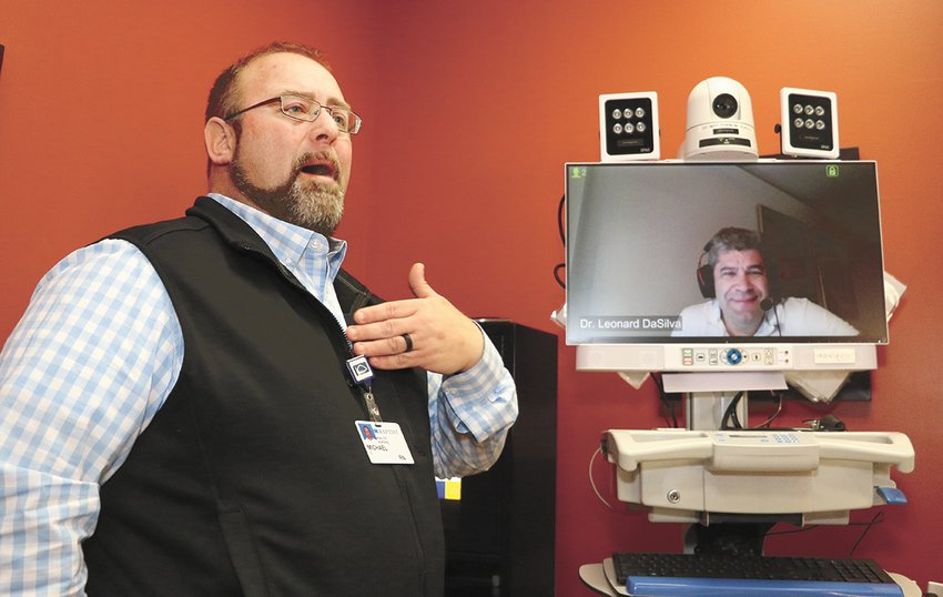 Michael Cupples, a registered nurse with Baptist-Carroll County, explains the telemedicine technology. On the monitor is Dr. Leonard DaSilva, who was in Hawaii at the time.