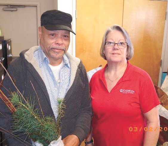 TREE GIVEAWAY — Carroll County Soil Conservation District secretary, Susan Bates (Right) presents Carroll County landowner, Stephen Pope of the Leach community free tree seedlings last year. Trees will be given away March 1.