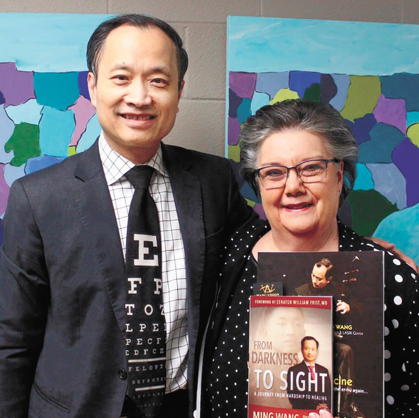 Dr. Ming Wang presents his book to Susan Sloan, director of the Carroll County Office on Aging. Wang, a world renowned eye surgeon, was born in communist China and was allowed to come to the states for a post-secondary education.