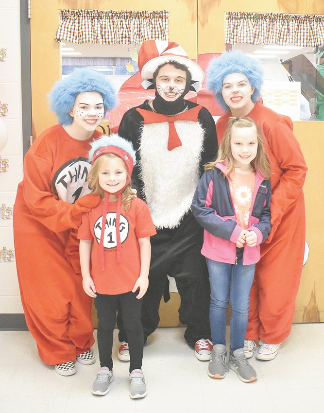 MES first graders Sami Mathis (left) and Abby Carroll hang out with The Cat in the Hat, Thing 1 and Thing 2 during the Read Across America celebration.