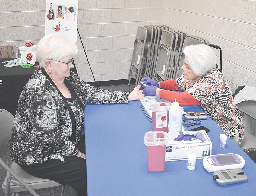 Pat Watkins (left) of McKenzie receives a free blood sugar and lipid profile administered by HCMC Medical Technologist Carolyn Chilcutt.
