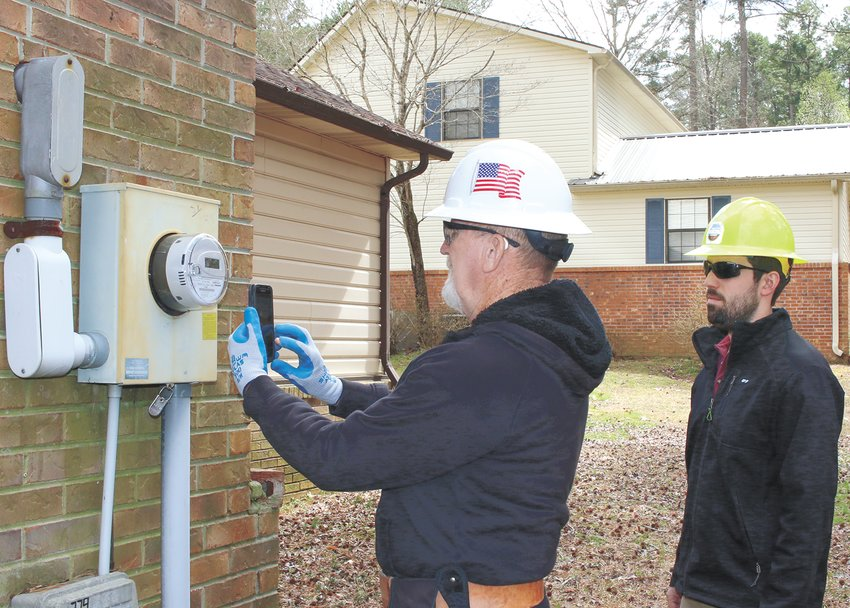 New  Honeywell Elster electric meters are being installed throughout Carroll County. The meters will transmit the customer's usage to the central office for monthly billing. Kenneth Peak, a contractor with Advance Meter Services installs the meter as Sam Owen of Carroll County Electric looks on.