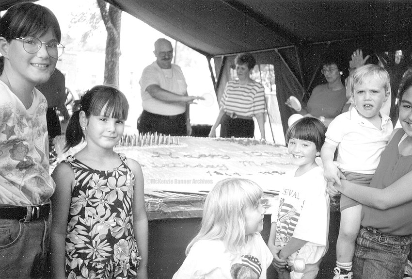 McKenzie celebrated its 125th birthday with a cake served at the City Recreational Park in 1994. Pictured are Bea Barksdale's grandchildren, J. T. Lindsey's grandchildren, Gary McKinnie, Ruby Allen, and Zia McKinnie.