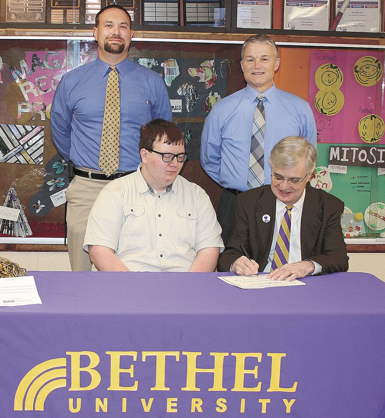 Edward Castleman, Jr. and Bethel President Walter Butler sign the Hendrix Scholarship contract as Gleason Principal Lee Lawrence and Weakley County Schools Director Randy Frazier look on.