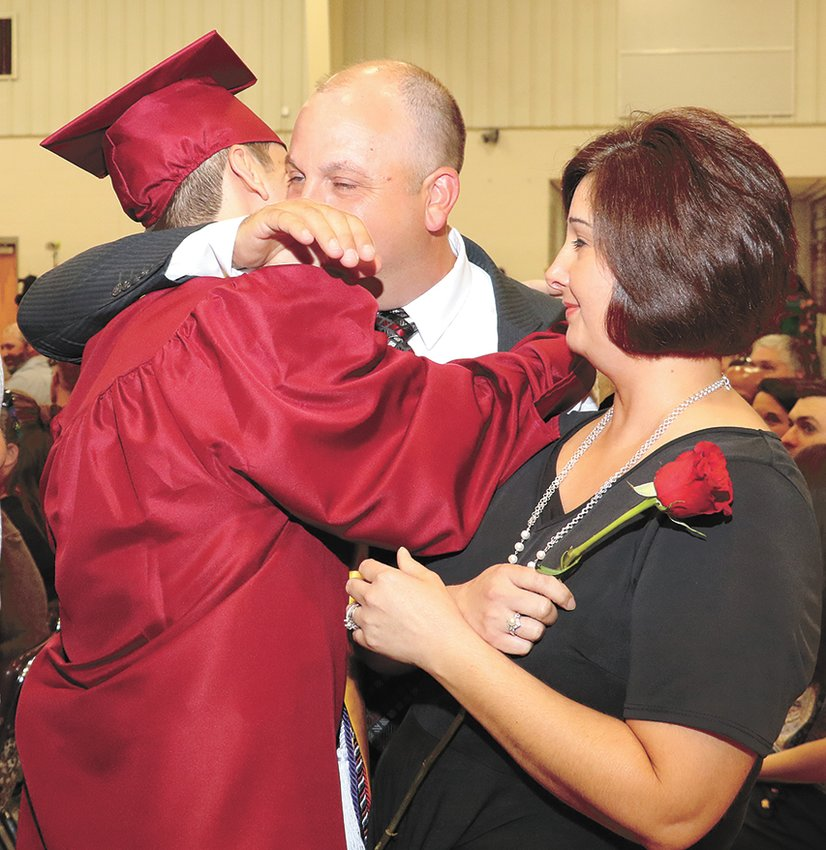 West Carroll graduate Jacob Mims presents a rose to his mom, Jenny, and gives his dad, Jared, and mom a hug.