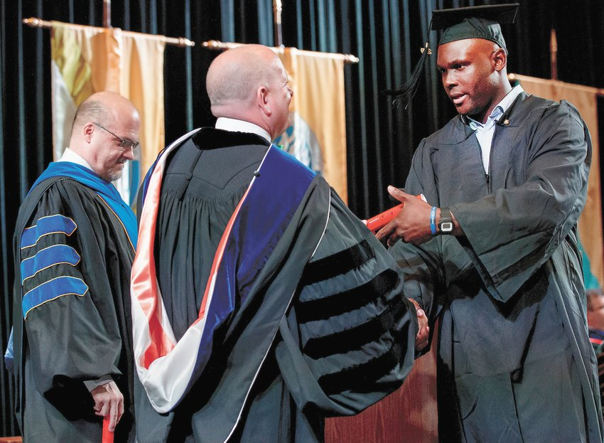Harry Evbuomwan, a current Huntingdon resident, accepts his diploma from UT Martin Chancellor Keith Carver during commencement exercises May 4.