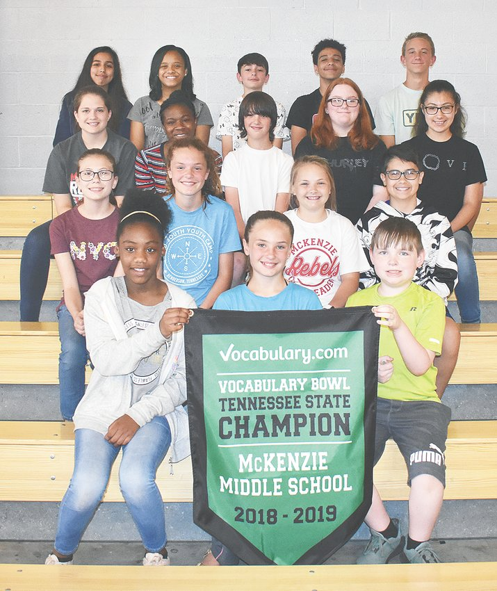 Several students from each grade display McKenzie Middle School's state championship banner. Pictured are (L to R): Front Row — fifth graders A'myiah Newbill, Sarah Luci and Seth Walker; Second Row — sixth graders Emma Smith, Allie Walker, Taylor Rawls and Guillermo Hickman; Third Row — seventh graders Nicole Gibson, Ma'Kya Taylor, Dakota Cary, Matilda Arnold and Jackelyne Padilla; Back Row — Yajaira Vega, Alajah Gilbert, Hunter Brasfield, Bryson Steele and Jackson Cassidy.