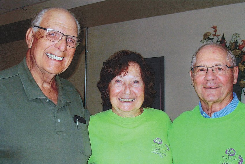 Club member Sara Fitzgerald (center) welcomes new members welcomes Larry Scott (left) and her husband Joe Fitzgerald to the Morning Glory Garden Club.