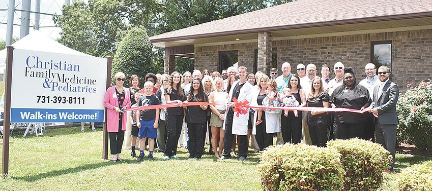 Drew Brown, PA, cuts the ribbon for Christian Family Medicine & Pediatrics. Pictured along the front row are (L to R): McKenzie Mayor Jill Holland; Briar Weatherly; Gage Weatherly; Abby Mayo, MA; Christine Hill, LPN; Kelsey Brown; Drew Brown, PA; Donna Waddell, FNP; Hattie Waddell; Candice Waddell; Delilah Waddell; Beth Ownby, RN; Raven Cunningham; and Carroll County Mayor Joseph Butler.