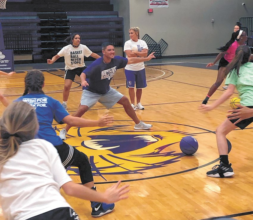Chris and Jennifer Nelson lead basketball campers in drills.