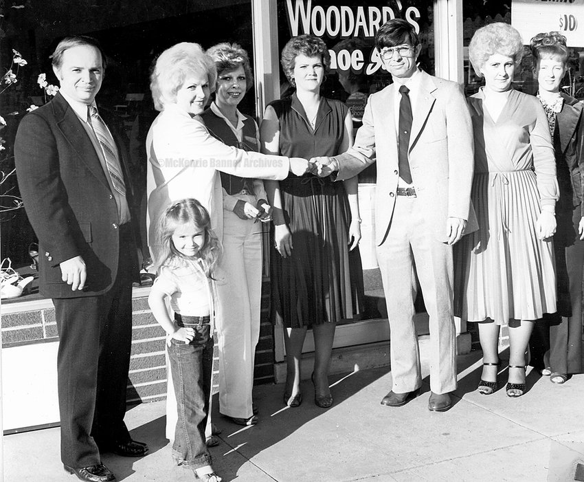 Bobby and Ann Dinkins and daughter, Angela accept the keys from former owners Ray and Barbara Woodard of Woodard's Shoes on Cedar St. Real estate agent Bonnie Marrison and employees, Robbie Adams and Kay Allen look on, early 1980s.