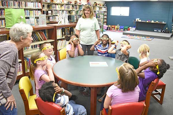 Kids (and adults) at the Carroll County Library's summer reading program display the steps for the sun's energy to power a light bulb.