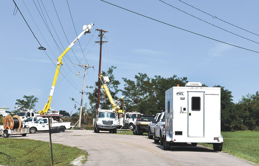 Crews from Carroll County Electric install new poles after an over-height mobile home snapped the poles.