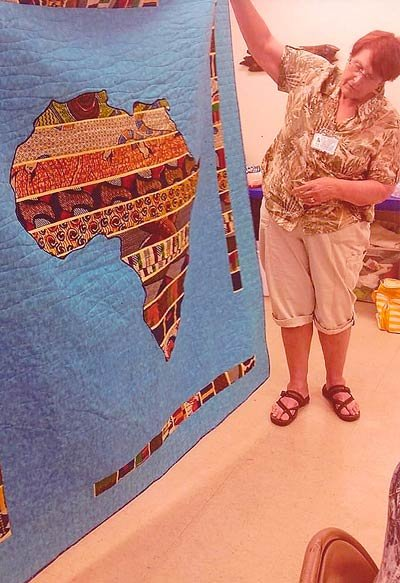 """Randi Stout shared her beautiful quilt, """"Out of Africa,"""" with members. Randi explained the problems she had with the unusual fabric she had received from Africa. She put a lot of thought into how she was going to use it. The map of Africa is beautiful and a compliment to the continent itself."""