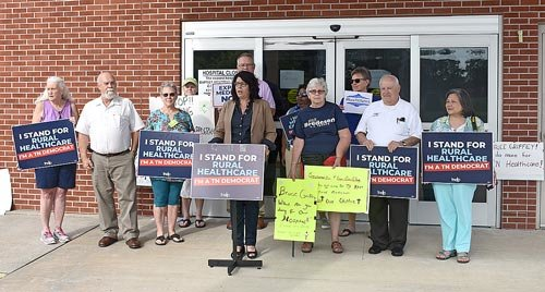 Tennessee Democratic Chairman Mary Mancini speaks in front of the former McKenzie Regional Hospital. Behind Mancini are members of the Democratic Party from Madison, Gibson, Weakley and Henry counties