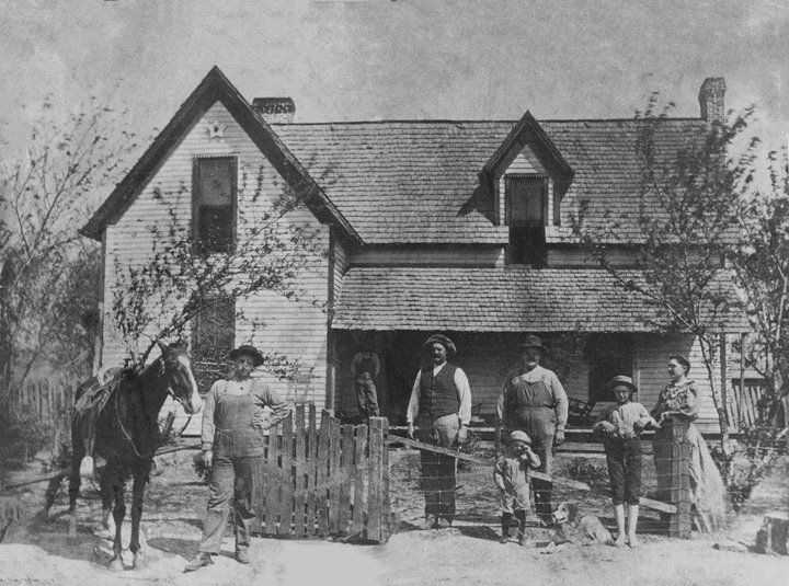 "Members of the Thomas Dinwiddie family in front of the old home place on Eli Brown Road, taken approximately 1911. (L to R): Badly (horse), Baker Parker Dinwiddie, Thomas ""Tom"" Dinwiddie (father), Thomas Roy Dinwiddie, George Weldon Dinwiddie, William Howard Dinwiddie, Ada Finley Dinwiddie (mother), Jim (dog) and Floyd Dinwiddie (relative on porch)."