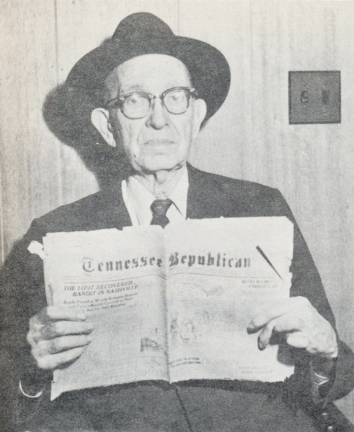 Former Carroll County Sheriff Sam Kennon holding a copy of the Tennessee Republican newspaper from 1923. The headline reads, LOOT RECOVERED: BANDIT IN NASHVILLE.