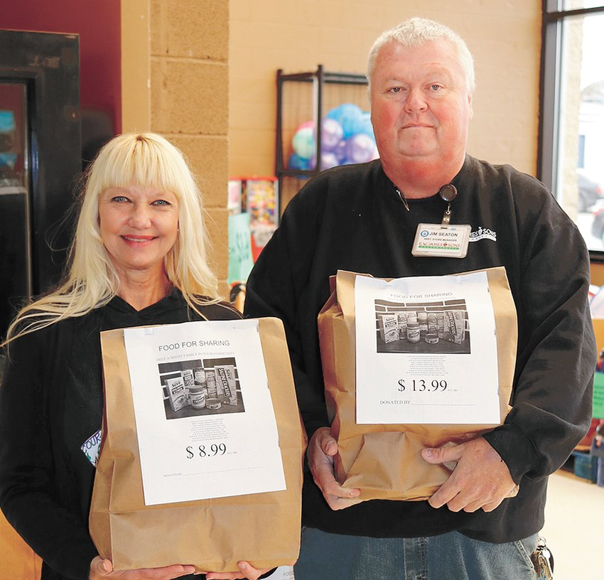 Saudia Akin, manager of McKenzie/Carroll County United Neighbors and Jim Seaton, assistant manager of E.W. James Supermarket in McKenzie display the two sizes of food bags available for purchase to help feed needy families in the community.