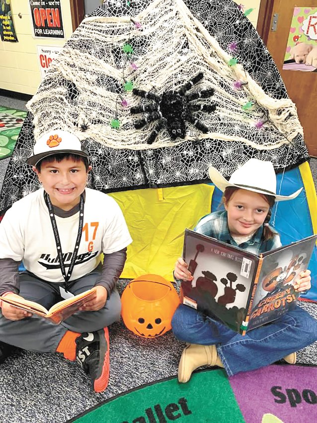 "(L to R) Second-graders Kaylor Pineda and Presley Scott, both in costume, enjoy reading in front of ""The Spooky House"" in the Gleason School Library during the week of Halloween for the Library's annual Read-in-the-Dark event."