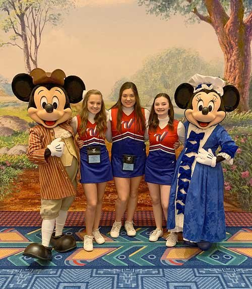 McKenzie Middle School cheerleaders (L to R) Brett Toombs, Ava Warman and Abbie Young meet Mickey and Minnie Mouse at the Thanksgiving Banquet.