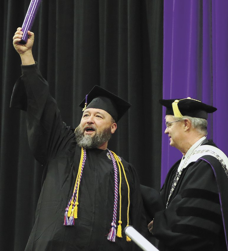 Timothy Lewis of Atwood shows his elation after receiving his diploma during Bethel commencement on Saturday. Dr. Walter Butler presented the diploma.