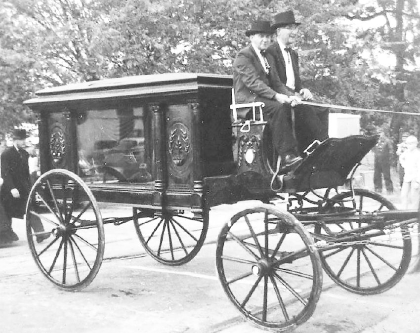 Horse-drawn hearse as it appeared in the 1969 Centennial Parade. The owner, Charles Penick, pictured on the right riding on the seat, purchased it when he bought Scates Undertakers and was used in his early years as a funeral director in McKenzie. It was stored in a barn on his property, cleaned by the family of Mr. Penick and friends who walked as mourners. It was sold to an undertaker in New York who saw it in the parade and later asked to purchase it. It is enclosed in glass and displayed in front of the New York business. It is in use today for special funeral requests in New York City.