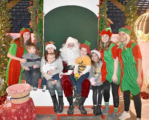Visiting Santa are (L to R): Eli Healy, three; Sarah Healy, ten; Nate Healy, one; Ethan Healy, four; and Mia Reynolds, seven, all of Dresden. Santa's helpers are (L to R): Tessa Stout, Haley Wheat and Sydney Shanklin, students at Westview High School
