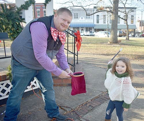 Mallie Whitworth, four, of McKenzie assists with a magic trick by Jason the Not-So-Great Magician (Jason Arnold of McKenzie) during McKenzie's Mistletoe Christmas.