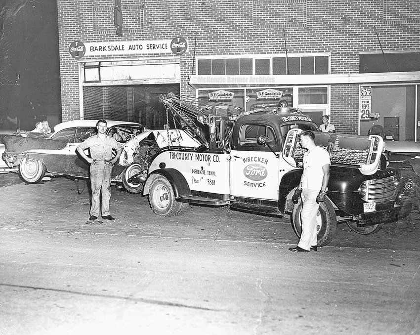 Barksdale Auto Service, Cedar St., 1955. Tri-County Motors Co.'s wrecker tows a '55 Olds. Front (L to R): Warren Barksdale; driver of wrecker is his brother, Kenneth Barksdale; in back is Warren's son, Kenneth W. Barksdale. Warren maintained a business relationship with Tri-County for many years, including the years he instructed students at the vocational school, who became employed by Tri-County Motors.
