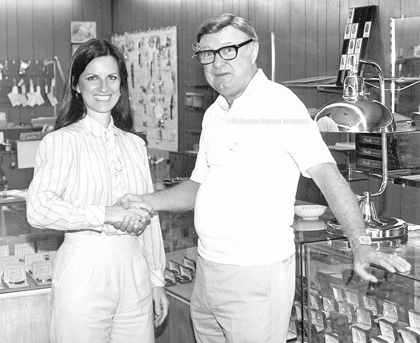Comb's Jewelers Owner, Milton Combs, presents the keys to new owner, Lynda Miller, 1980. Miller and her husband, Kenneth, owned and operated Miller's Jewelers on Cedar Street.