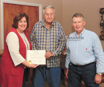Terry Frazier presents Jerry Dunlap with his high school diploma as Charles Bookout looks on.